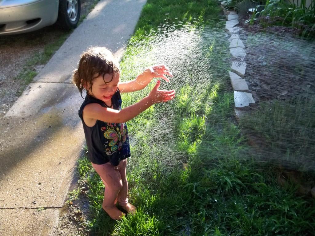 toddler in sprinkler