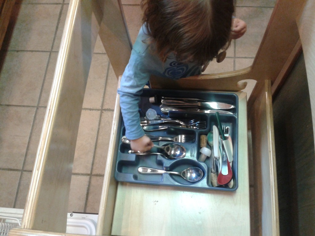 toddler putting away silverware