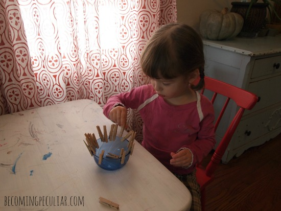 Practicing with clothespins on a bowl: Montessori activities for a 2-year-old