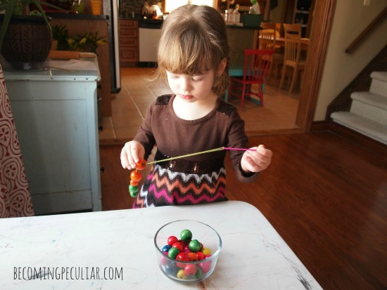 Stringing wooden beads onto embroidery thread: Montessori activities for a two-year-old